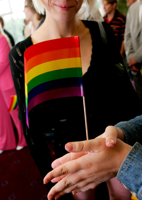two people hold a small rainbow flag together