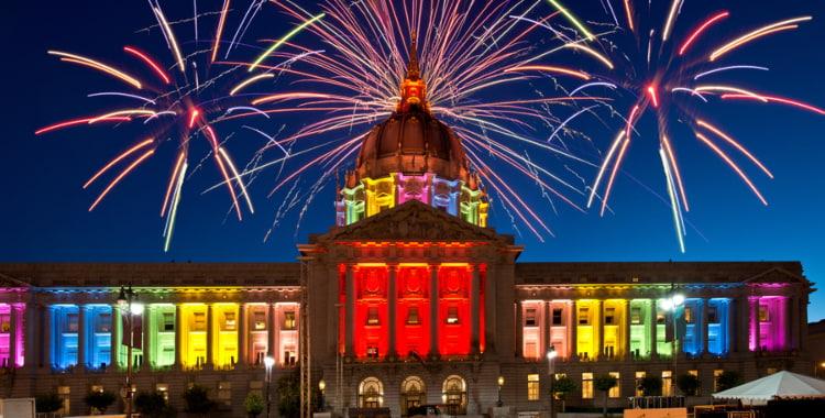 fireworks burst behind a rainbow san francisco city hall