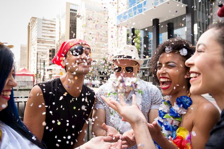friends throw confetti during carnaval san francisco