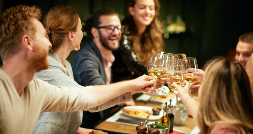 A group of people toasting wine at a dining table