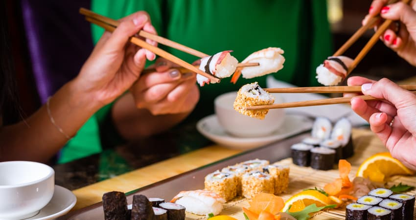 A group of people holding sushi with chopsticks at a restaurant