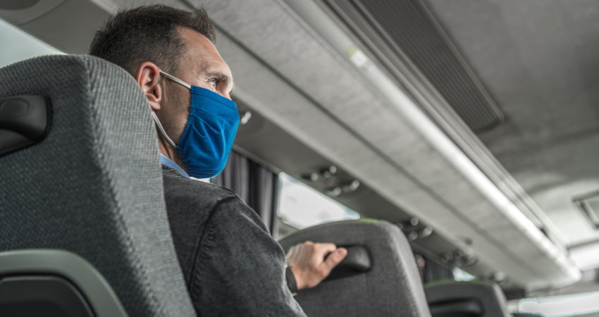 A man in a suit wears a mask while traveling on a charter bus