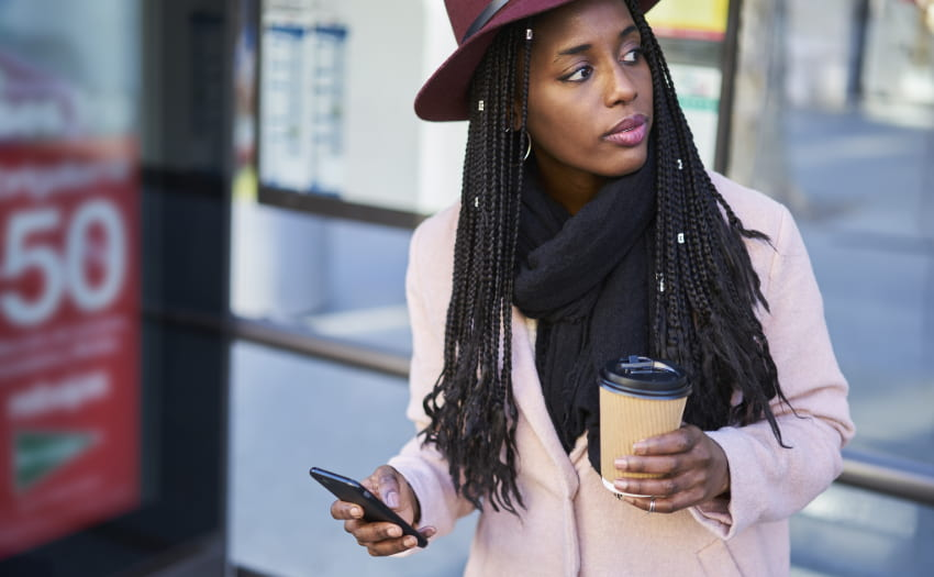A woman stands at a bus station with her coffee as she commutes to work