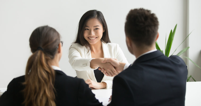 A woman shakes hands with a potential employer after a successful interview