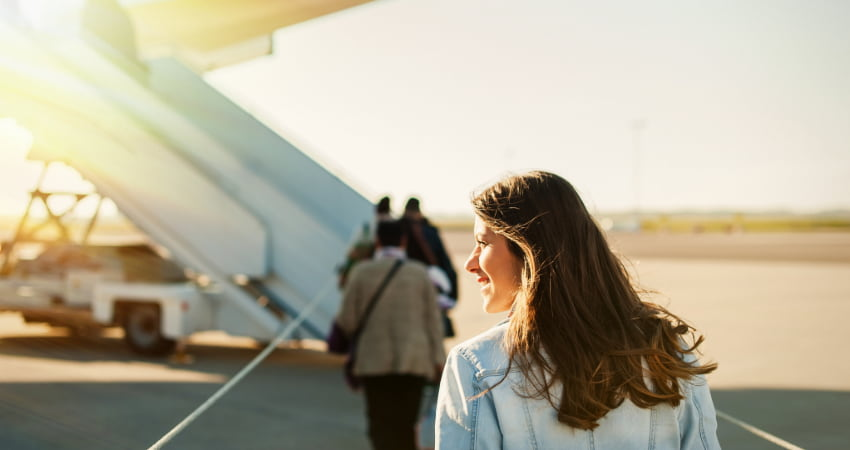 A woman boards a plane from an outdoor ramp