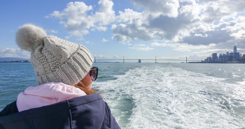 A passenger in a winter cap rides the ferry between Alcatraz and the San Francisco mainland