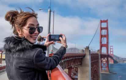 A woman taking a selfie photo while walking the Golden Gate Bridge