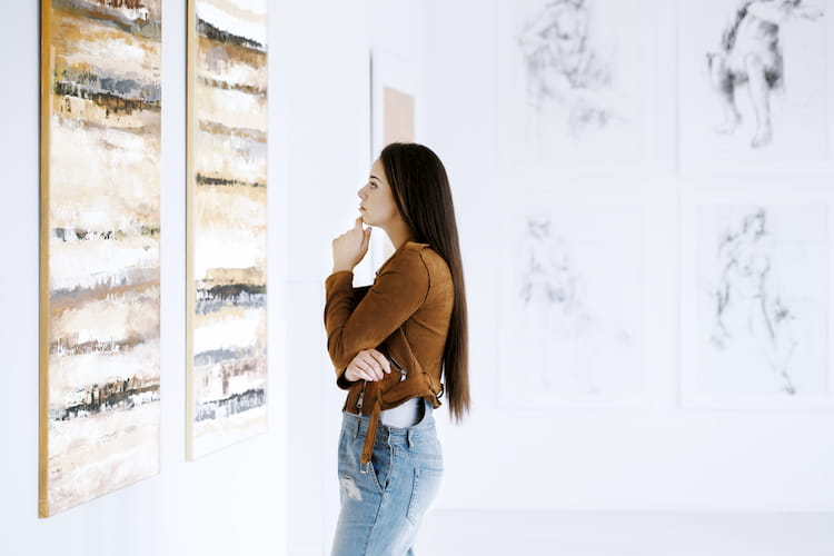 a woman looks at a gallery painting and thinks