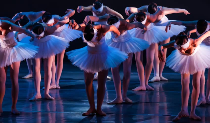 A large group of ballet dancers perform on a dark stage