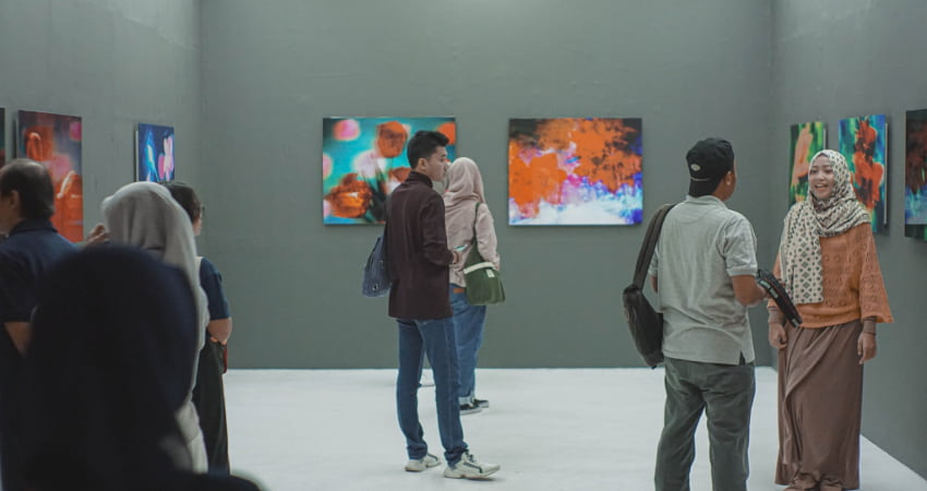 A crowd of art lovers stand and chat in a gallery filled with bright paintings