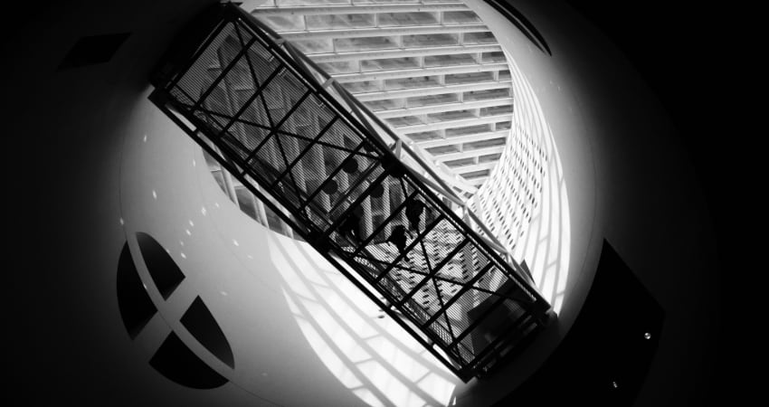 A black and white photo looking up at a suspended walkway inside the San Francisco Museum of Modern Art