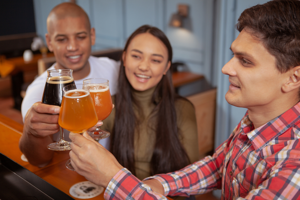 Friends clinking glasses of beer at bar