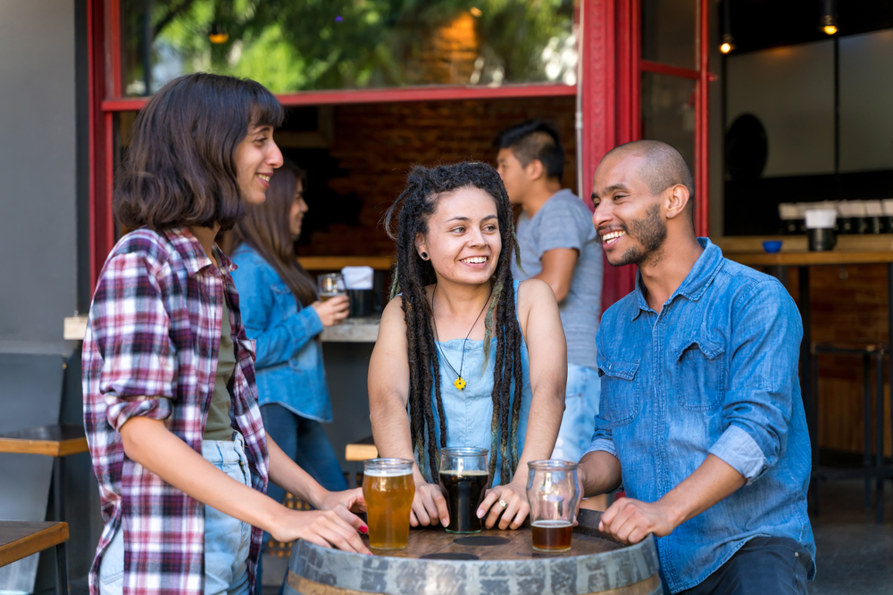Friends around barrel table at brewery