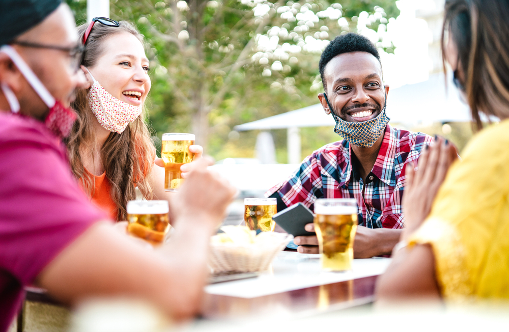 Friends drinking outside with masks lowered