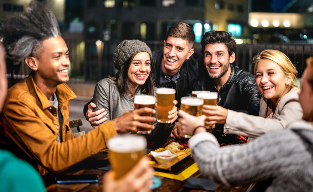 Friends toasting with beer outside of bar