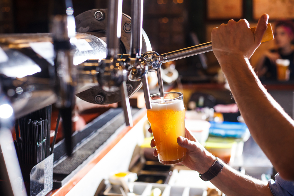 A bartender pours beer from a tap
