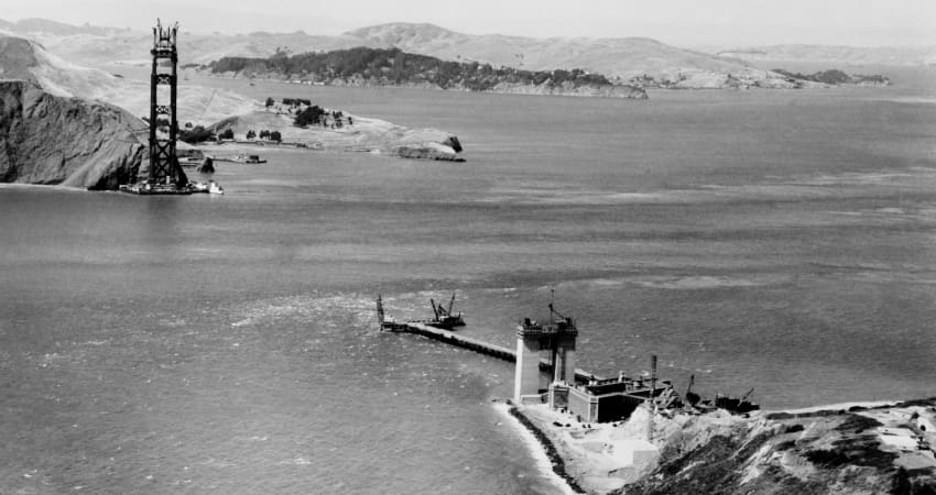 A black and white photo from 1932 as the Golden Gate Bridge is being constructed across the bay