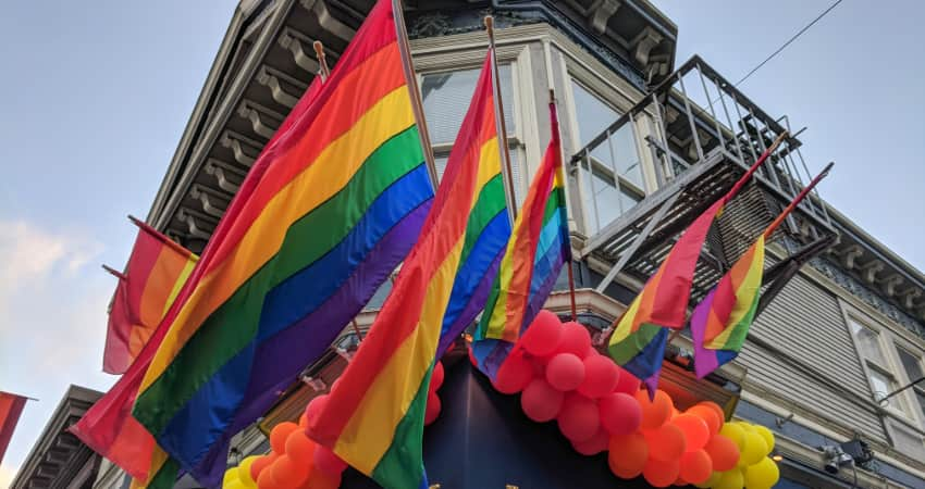 Rainbow flags and balloons hang outside a building in San Francisco