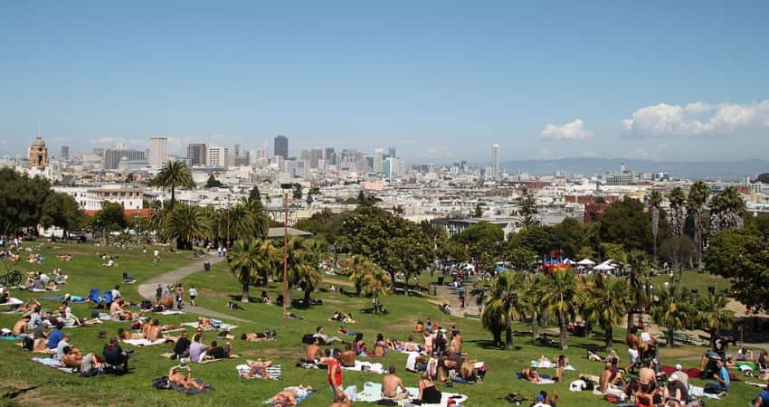 Dozens of people sunbathing on a hill in Dolores Park with the San Francisco skyline in the background
