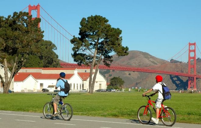 Two bikers ride past a viewpoint of the Golden Gate Bridge in the Presidio