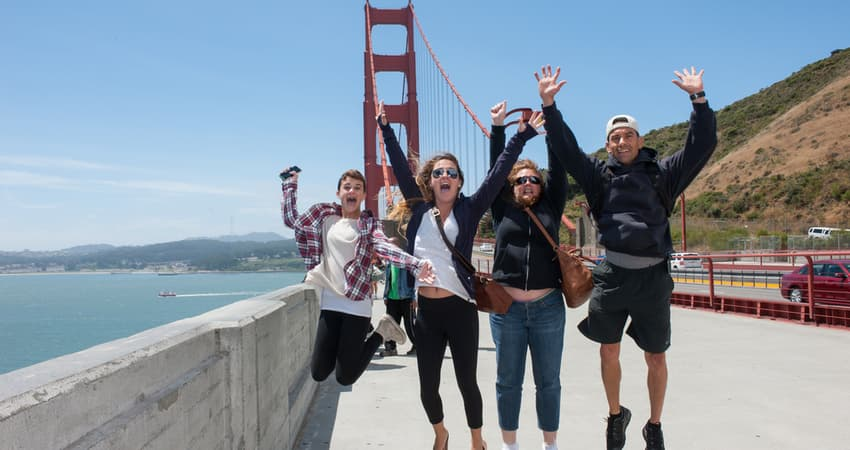 A group of friends jumping and smiling in front of the Golden Gate Bridge