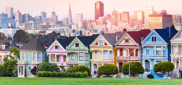 """san francisco's """"painted ladies"""" houses in pink, green, yellow, red, and blue, all in a row"""