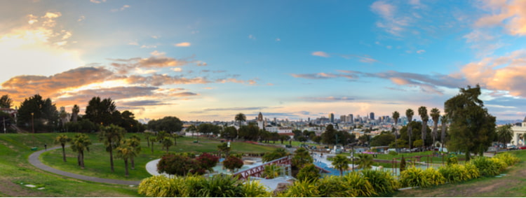 an aerial view of mission dolores park, with lots of green space, trees, and the city buildings in the background
