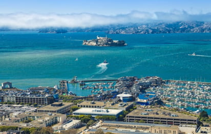 an aerial view of fisherman's wharf with alcatraz and mountains in the distance
