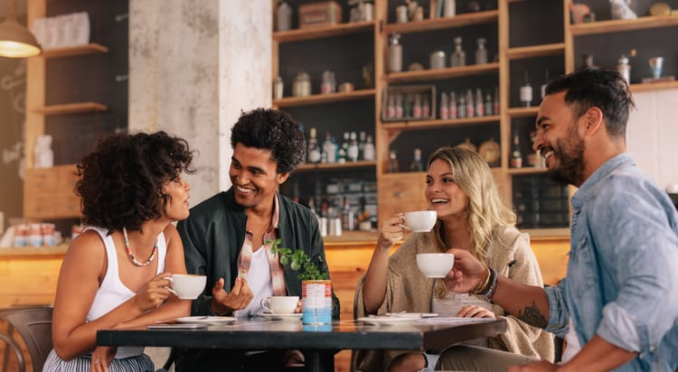 friends laugh and hold coffee cups at a table in a cafe