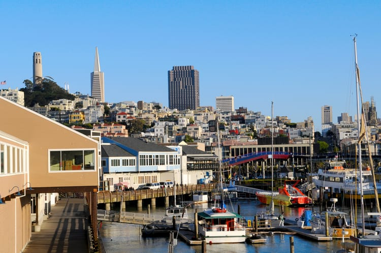 pier 39 at fisherman's wharf, with buildings on stilts int he water and the city in the background