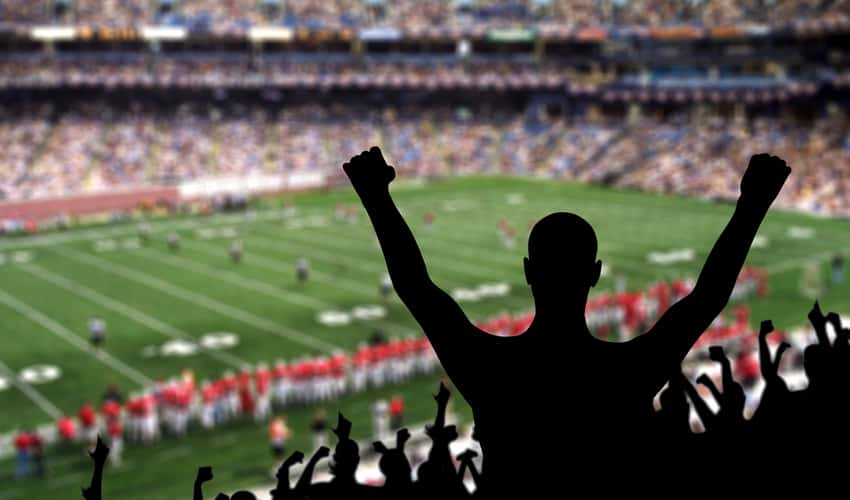 Fans cheering in a football stadium at a college game